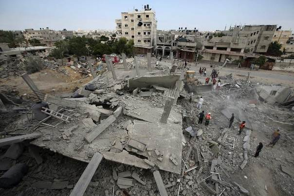 Palestinians gather as rescue workers search for victims under the rubble of a house which witnesses said was destroyed in an Israeli air strike, in Rafah in the southern Gaza Strip August 4, 2014. REUTERS/Ibraheem Abu Mustafa