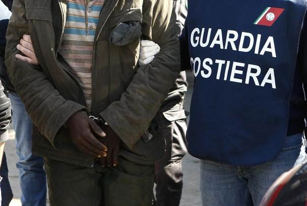 A man suspected of being a human trafficker is taken away in handcuffs by Italian Coast Guards at the Sicilian port of Augusta near Siracusa, Italy, March 21, 2014. REUTERS/Antonio Parrinello