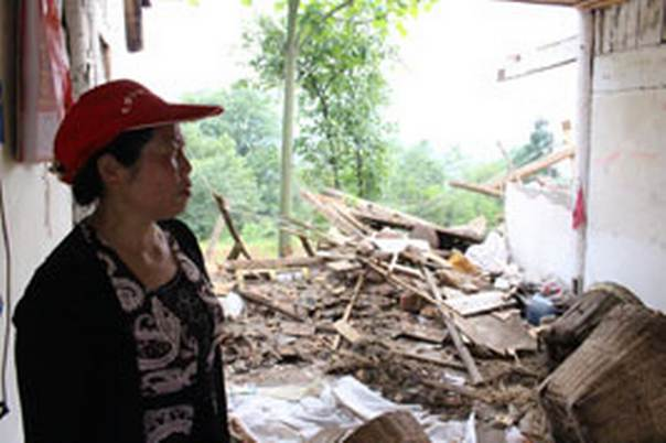 Wang Xing Wiong stands inside her damaged home in Maping village, Tiantaishan town, Qionglai city. Photo courtesy of Andy Chong / Habitat for Humanity China