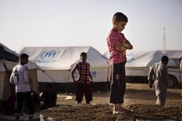 A boy, who fled from the violence in Mosul, stands near tents in a camp for internally displaced people on the outskirts of Arbil in Iraq's Kurdistan region June 14, 2014 REUTERS/Jacob Russell