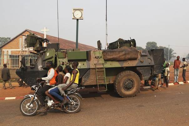 People ride on a motorcycle as they pass past a military vehicle in Wouango district, Central African Republic, January 9, 2014. REUTERS/Emmanuel Brau
