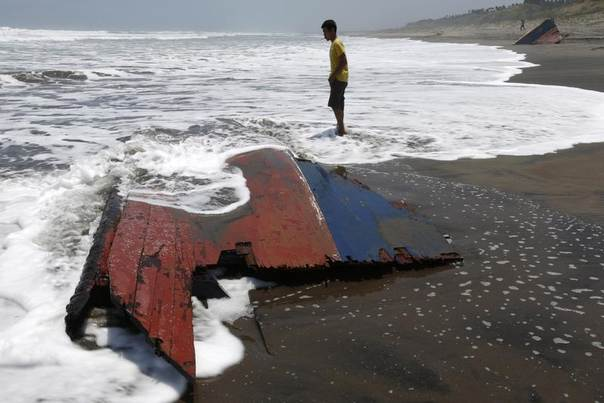 A youth stands near a piece of wreckage of a boat which sank off the Indonesian coast, at Agrabinta beach on the outskirts of Sukabumi, Indonesia's West Java province, September 28, 2013. The boat carrying migrants to Australia sank off the Indonesian coast, killing at least 21 people, Indonesian police said.REUTERS/Beawiharta