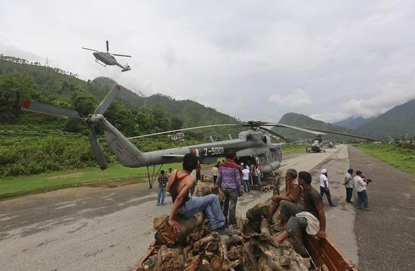Volunteers wait to unload wood from a truck to be used for mass cremation at Kedarnath at an airport in Gauchar in the Himalayan state of Uttarakhand June 25, 2013. REUTERS/Danish Siddiqui