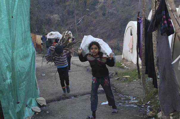 A Syrian refugee girl carries a bag of wood in the al-Yamdiyeh refugee camp near the Syrian-Turkish border in Latakia province January 10, 2014. REUTERS/Khattab Abdulaa