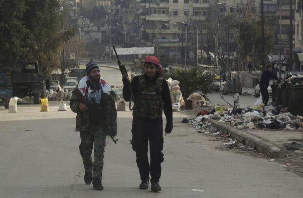 Syrian rebel fighters hold their weapons as they walk along a street in Aleppo's Salaheddine neighbourhood, Syria, January 10, 2014. REUTERS/Hosam Katan