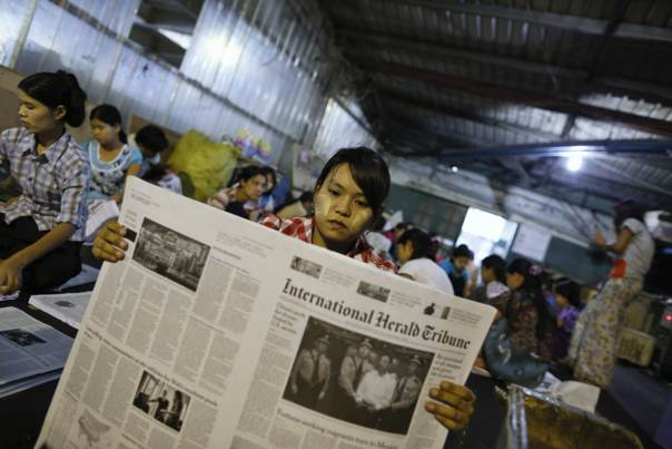 A worker arranges pages of the International Herald Tribune newspaper, which is printed for the first time in Myanmar, in Yangon, on Sept. 23, 2013. REUTERS/Soe Zeya Tun