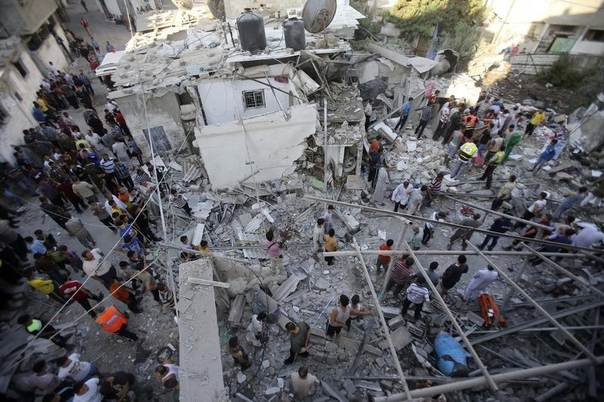 Rescue workers search for victims as Palestinians gather around the wreckage of a house, which witnesses said was destroyed in an Israeli air strike that killed at least nine members from the al-Ghol family, in Rafah in the southern Gaza Strip August 3, 2014. REUTERS/Ibraheem Abu Mustafa