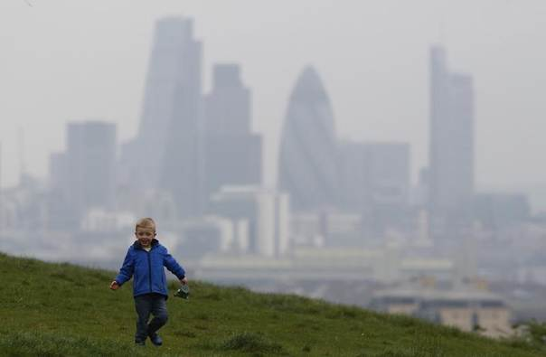 Daniel Buttery, 4, plays in Greenwich Park as a haze of pollution sits over the London skyline, April 3, 2014. REUTERS/Luke MacGregor