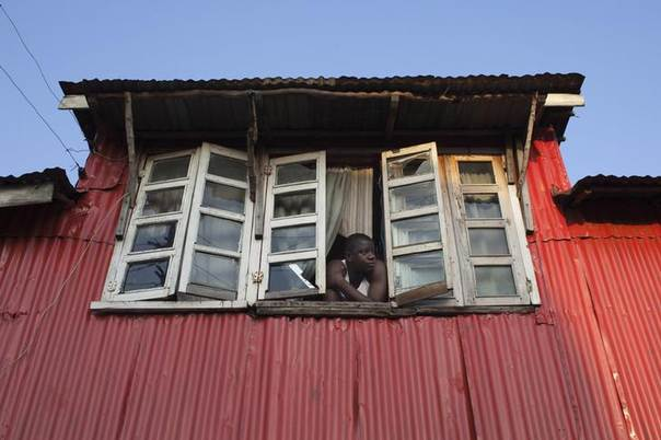 A man looks out of the window of his colonial-era house in Freetown, Sierra Leone November 19, 2012. REUTERS/Joe Penney