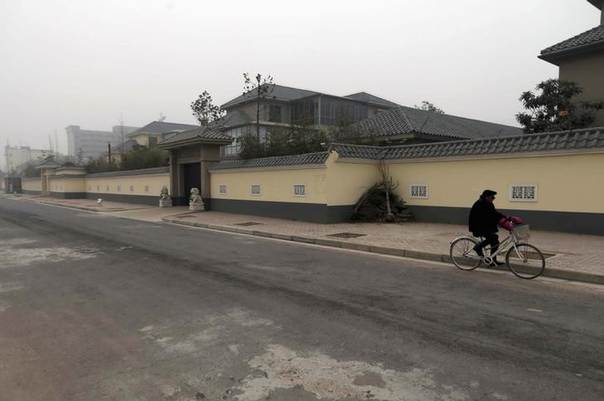 A man cycles past an unfinished residence which belongs to former People's Liberation Army (PLA) General Gu Junshan, in Puyang, Henan province January 19, 2014