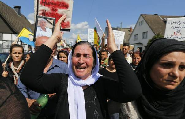 A Kurdish women of the ethnic minority of Yazidis cries as she marches through the streets of Bielefeld, Germany, during a demonstration, August 9, 2014. REUTERS/Wolfgang Rattay