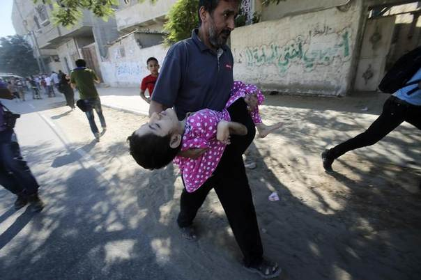 A Palestinian man carries his disabled son as they flee their house during what witnesses said was heavy Israeli shelling, in Rafah in the southern Gaza Strip August 1, 2014. REUTERS/Ibraheem Abu Mustafa