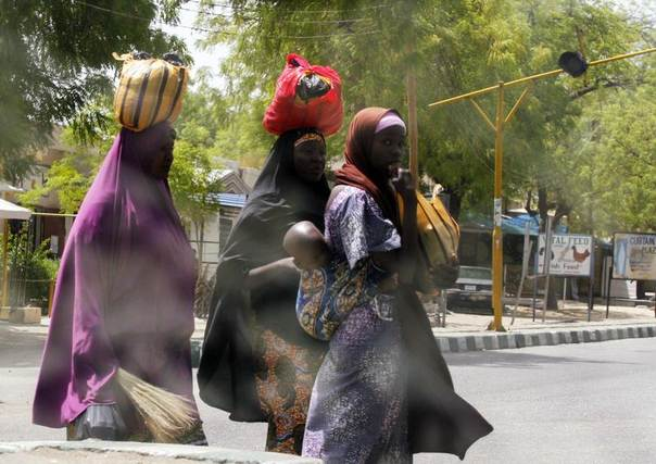 Women cross a road with their belongings in Maiduguri in Borno State, May 19, 2013. REUTERS/Afolabi Sotunde