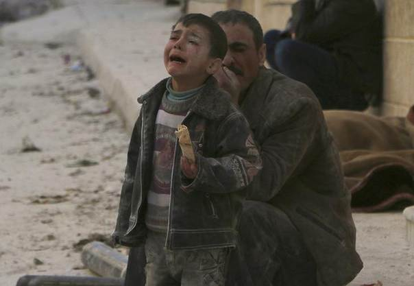 A boy cries at a site hit by what activists say was an airstrike by forces loyal to Syrian President Bashar al-Assad in Masaken Hanano in Aleppo February 14, 2014. REUTERS/Hosam Katan