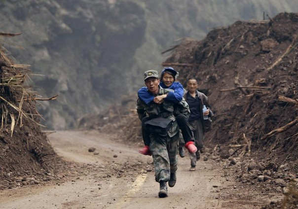 A Chinese soldier carries an earthquake survivor