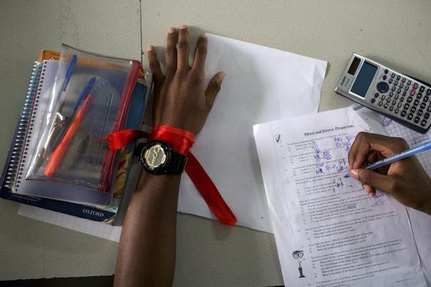 A student wears a red ribbon to express solidarity with the abducted Nigerian schoolgirls from the remote area of Chibok, as he does a maths exercise at the Regent Secondary School in Abuja, May 14, 2014 REUTERS/Joe Penney