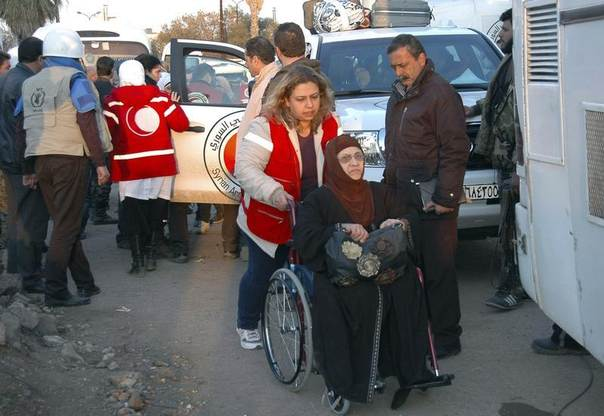 A member of the Syrian Arab Red Crescent helps a woman from a besieged area of Homs upon her arrival to the area under government control February 9, 2014, in this handout released by Syria's national news agency SANA. REUTERS/SANA/Handout via Reuters