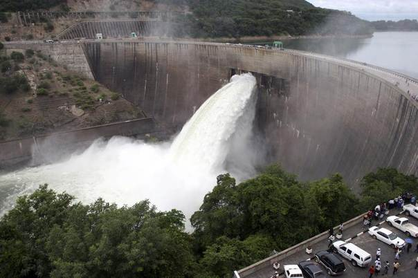 People watch as the spillway gates of another Zimbabwe dam - the Kariba North Bank dam on Lake Kariba - are opened to reduce rising water levels in February 2008. REUTERS/Mackson Wasamunu