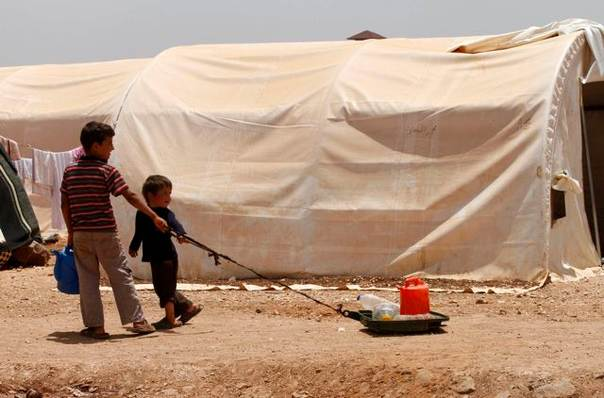 Syrian children pull water bottles at the Bab Al-Salam refugee camp in Azaz, near the Syrian-Turkish border, on June 9, 2013. REUTERS/Hamid Khatib