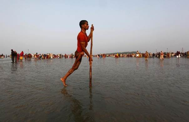 A polio affected man returns after taking a dip at the confluence of the Ganges river and the Bay of Bengal at Sagar Island, south of Kolkata, India, January 13, 2012. REUTERS/Rupak De Chowdhuri