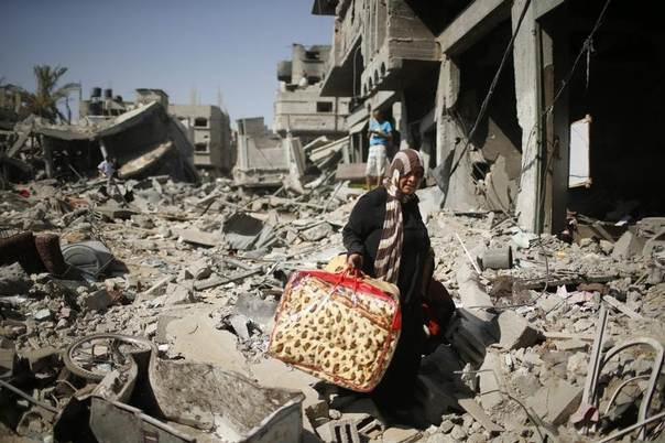 A Palestinian woman carries her belongings from her destroyed house in the Shejaia neighborhood, which witnesses said was heavily hit by Israeli shelling and air strikes during an Israeli offensive in the east of Gaza City, August 1, 2014.  REUTERS/Mohammed Salem