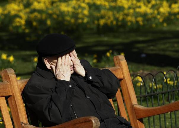 An elderly man rubs his face as he sits in the spring sunshine in St James's Park in London, March 8, 2012. REUTERS/Luke MacGregor