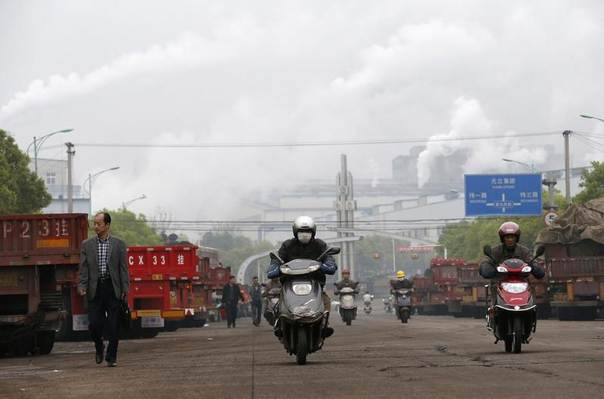 Motorbikes ride along a street near chimneys with rising smoke on a hazy day in Quzhou, Zhejiang province, China, April 1, 2014. REUTERS/William Hong