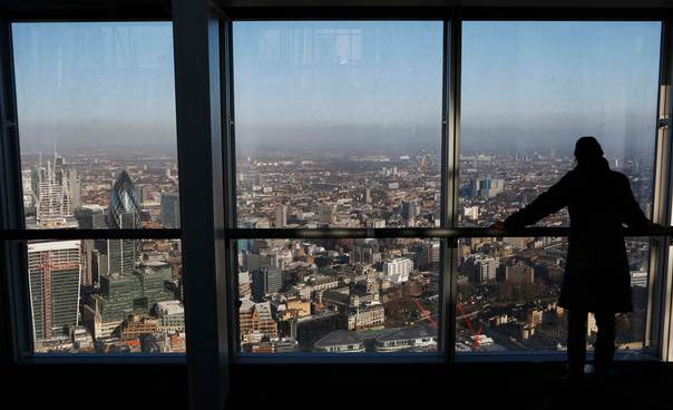 A woman looks out at the financial district from a window in The View gallery at the Shard, western Europe's tallest building, in London on Jan. 9, 2013. REUTERS/Luke Macgregor