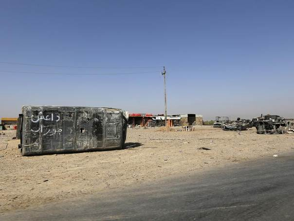 Burnt vehicles belonging to the Iraqi security forces are seen on a road leading to Samarra at Salahuddin province July 12, 2014. REUTERS/Thaier Al-Sudani