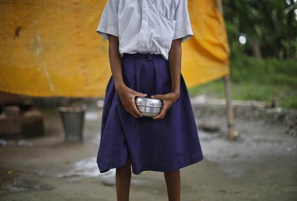 A schoolgirl holds a container to receive her free mid-day meal, distributed by a government-run primary school, at Brahimpur village in Chapra district of the eastern Indian state of Bihar, India, July 19, 2013. REUTERS/Adnan Abidi