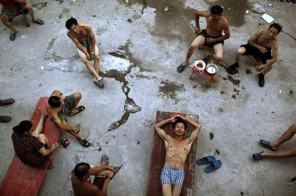 Migrant construction workers relax in the evening breeze outside their dormitories after a shift at a residential construction site in Shanghai August 12, 2013. REUTERS/Aly Song