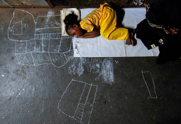 Noor Jahan, 5, sleeps on chalk drawings she made as her mother begs for alms at a railway station in Mumbai, on Dec. 7, 2012. REUTERS/Danish Siddiqui