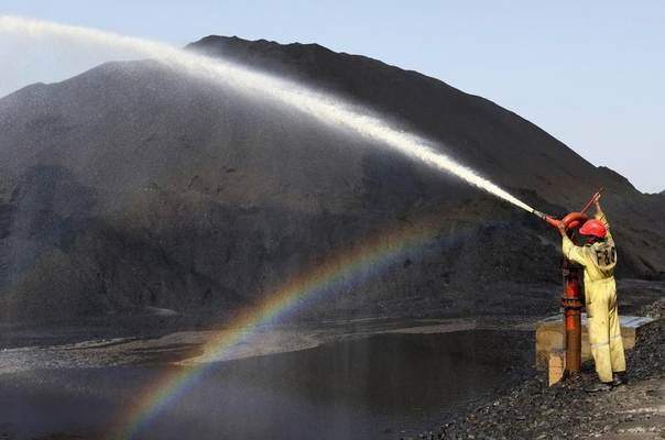 A worker sprays water over piles of coal at Mundra Port Coal Terminal in the western Indian state of Gujarat, April 2, 2014. REUTERS/Amit Dave