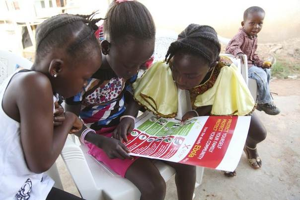 Girls look at a poster, distributed by UNICEF, bearing information on and illustrations of best practices that help prevent the spread of Ebola virus disease (EVD), in the city of Voinjama, in Lofa County, Liberia in this April 2014 UNICEF handout photo. REUTERS/Ahmed Jallanzo/UNICEF/Handout via Reuters