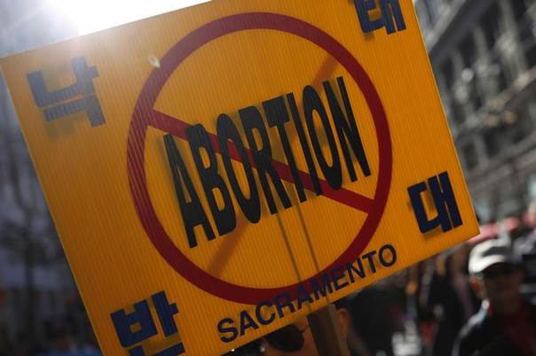 An anti-abortion sign is seen as demonstrators march on Market Street during the Ninth Annual Walk for Life West Coast rally in San Francisco, California, January 26, 2013. REUTERS/Stephen Lam