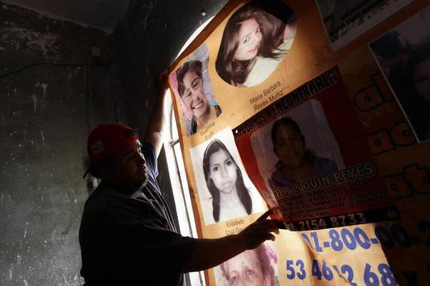 A man hangs up a banner showing photographs of missing and dead women in Ecatepec, Mexico, April 23, 2013. REUTERS/Henry Romero