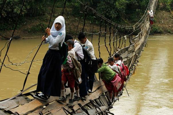 Students hold on to the side steel bars of a collapsed bridge as they cross a river to get to school at Sanghiang Tanjung village in Lebak regency, Indonesia's Banten village on January 19, 2012. REUTERS/Beawiharta