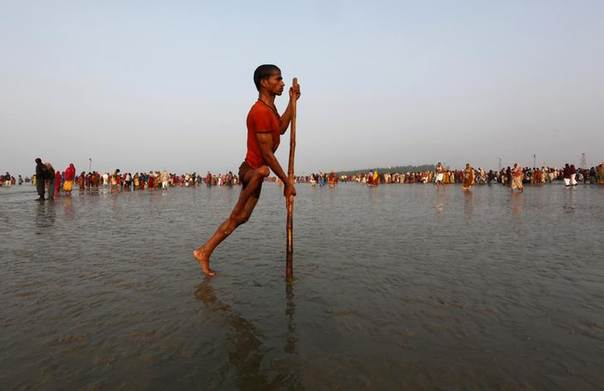 A polio affected man returns after taking a dip at the confluence of the Ganges river and the Bay of Bengal, January 13, 2012.  REUTERS/Rupak De Chowdhuri
