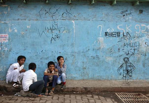 Boys sit next to a wall in Dharavi, one of Asia's largest slums, in Mumbai January 24, 2014. REUTERS/Mansi Thapliyal