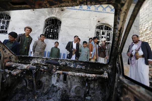 People look at a vehicle destroyed during a police raid on a hideout of al Qaeda militants in the Arhab region, north of the Yemeni capital Sanaa May 27, 2014. REUTERS/Khaled Abdullah