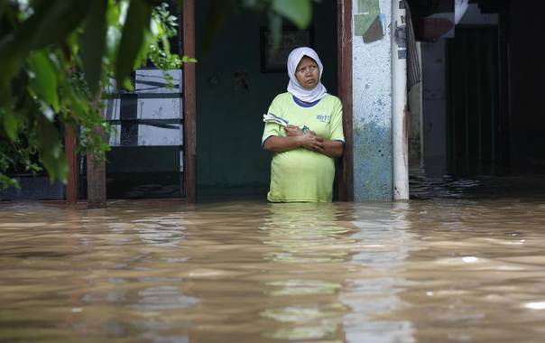 An Indonesian woman stands in front of her flooded house in Jakarta, Jan. 17, 2013. REUTERS/Enny Nuraheni