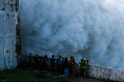 People watch as Hoa Binh hydroelectric power plant opens the flood gates after a heavy rainfall caused by a tropical depression in Hoa Binh province outside Hanoi