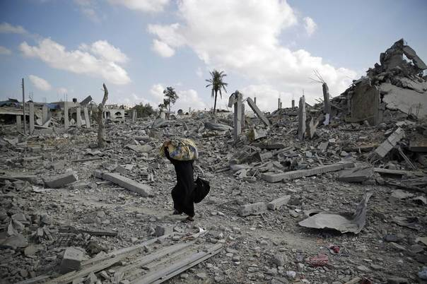 A Palestinian woman carries belongings while walking over the rubble of buildings destroyed by what police said were Israeli air strikes and shelling in Khuzaa, east of Khan Younis, in the southern Gaza Strip August 3, 2014. REUTERS/Finbarr O'Reilly