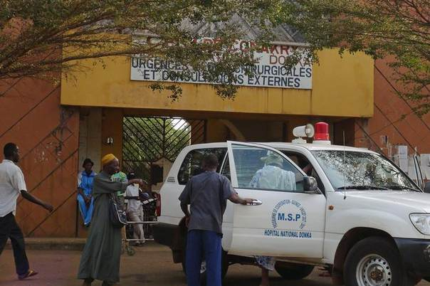 People walk in front of the entrance of the Donka Hospital, where victims of the ebola disease are being treated, in Conakry March 28, 2014. REUTERS/Saliou Samb