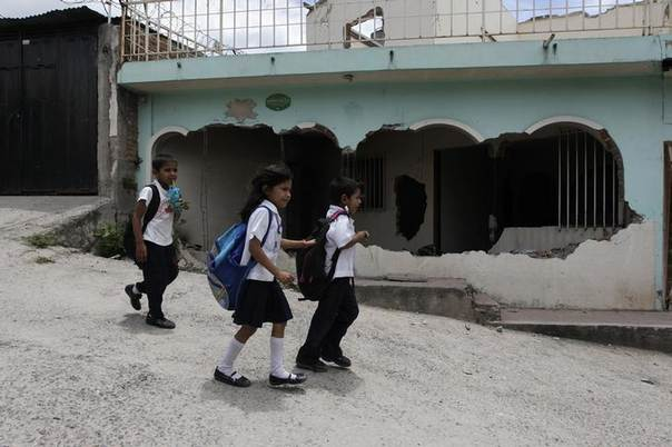 Children walk past an abandoned house in the gang-infested 14 de Marzo neighbourhood in Tegucigalpa, Honduras. Picture May 23, 2014, REUTERS/Jorge Cabrera
