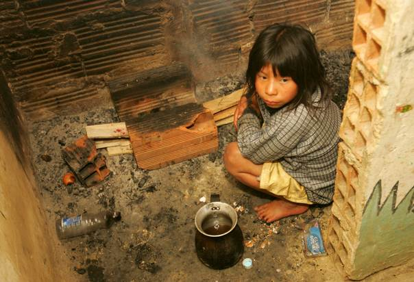 In a 2005 file photo, Colombian Embera-Catios Indian, Melba Sintua, sits in a kitchen in Cazuca near Bogota.  Thousands of Embera Indians have fled their rainforest reserves since mid-May 2014 to escape fighting between drug gangs and the National Liberation Army (ELN), Colombia's second-biggest guerrilla group. REUTERS/Eliana Aponte