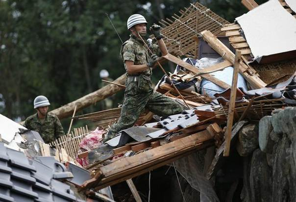 Japan Self-Defense Force (JSDF) soldiers search for survivors at a site where a landslide swept through a residential area at Asaminami ward in Hiroshima, western Japan, August 20, 2014. REUTERS/Toru Hanai