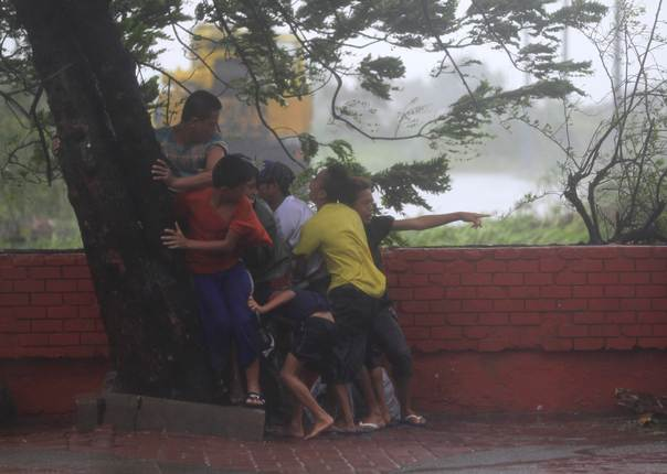 People take cover under a tree after strong winds brought by Typhoon Rammasun, locally called Glenda, battered the capital, metro Manila July 16, 2014. Philippine authorities evacuated almost 150,000 people from their homes and shuttered financial markets, government offices, businesses and schools on Wednesday as typhoon Rammasun gathered strength and hit the capital, Manila. REUTERS/Romeo Ranoco