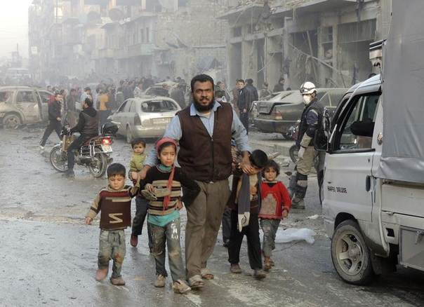 A man walks with children at a site hit by what activists said were barrel bombs dropped by government forces in Aleppo's Dahret Awwad neighbourhood January 29, 2014. REUTERS/Hosam Katan