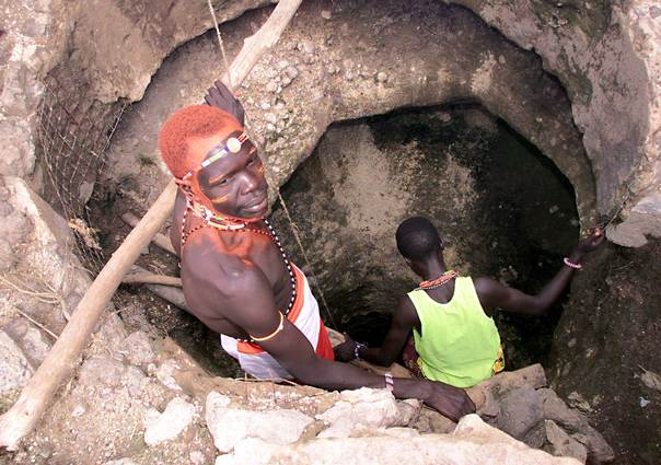 A Turkana warrior helps women and children draw water from a deep well within the Samburu National Reserve in northern Kenya May 11, 2002.